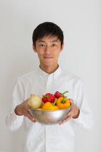 室内で野菜の入ったカゴを持つ男性の写真素材 [FYI01726405]