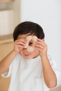 室内でドーナツの穴から覗く子供の写真素材 [FYI01726408]
