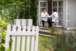 ベランダで椅子に座りコーヒーブレイクをする笑顔の夫婦の写真素材 [FYI01726442]