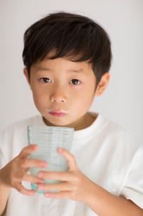 室内でコップの牛乳を飲む子供の写真素材 [FYI01726444]