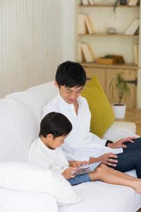 リビングのソファでタブレット端末を使う子供とパパの写真素材 [FYI01726453]