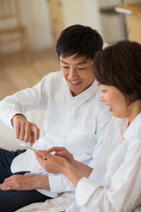 リビングのソファでスマートフォンを使用する夫婦の写真素材 [FYI01726510]
