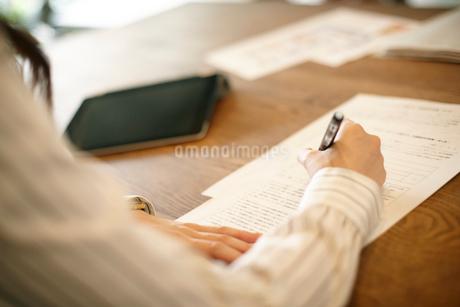 書類に記入する女性の手元の写真素材 [FYI01726515]