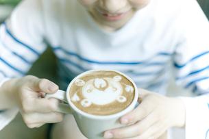 ラテ・アートされたエスプレッソコーヒーを飲む女性の写真素材 [FYI01726518]