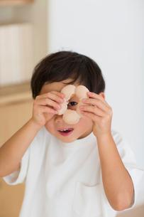 室内でドーナツの穴から覗く笑顔の子供の写真素材 [FYI01726548]