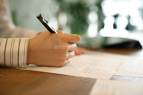 書類に記入する女性の手元の写真素材 [FYI01726561]