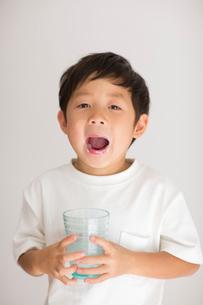 室内でコップの牛乳を飲み干した子供の写真素材 [FYI01726608]