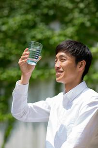 庭でコップの水を眺める笑顔の男性の写真素材 [FYI01726650]