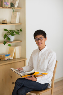 室内で本を読む男性の写真素材 [FYI01726689]