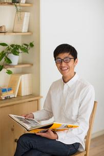 室内で本を読む笑顔の男性の写真素材 [FYI01726714]