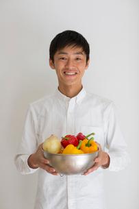 室内で野菜の入ったカゴを持つ笑顔の男性の写真素材 [FYI01726750]
