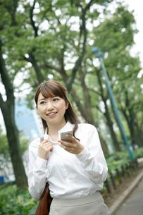 スマートフォンを手にしているビジネスウーマンの写真素材 [FYI01726752]