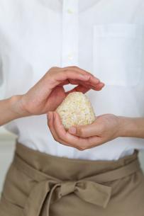 玄米のおむすびを握る手元の写真素材 [FYI01726765]