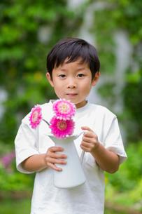 庭で花瓶の花を持つ子供の写真素材 [FYI01726872]