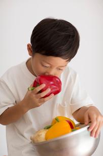 室内で野菜の入ったカゴを持ちパプリカを嗅ぐ子供の写真素材 [FYI01726904]