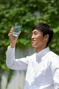 庭でコップの水を眺める男性の写真素材 [FYI01726990]