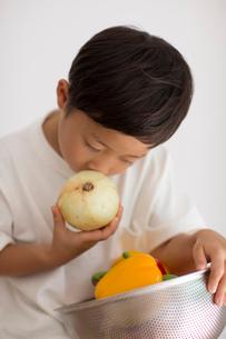 室内で野菜の入ったカゴを持ち玉ねぎを嗅ぐ子供の写真素材 [FYI01726997]