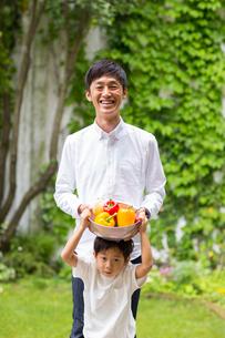 庭で野菜入りのカゴを笑顔で持つ父と子の写真素材 [FYI01727012]
