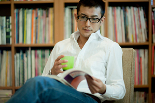 本棚の前で読書する眼鏡をかけた男性の写真素材 [FYI01727869]
