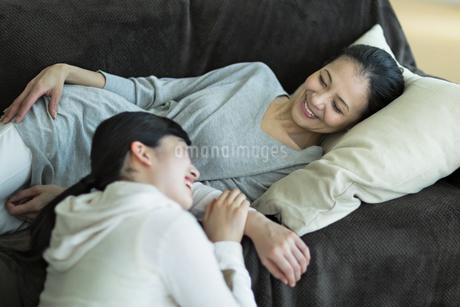 ソファーでくつろぐ母親と娘の写真素材 [FYI01733073]