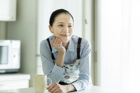 頬杖をついて微笑む女性の写真素材 [FYI01733092]