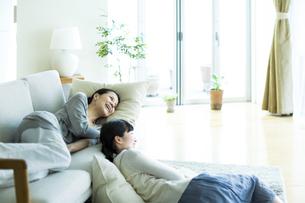 ソファーでくつろぐ母親と娘の写真素材 [FYI01733131]