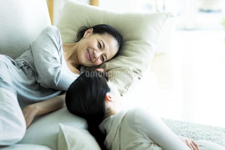 ソファーでくつろぐ母親と娘の写真素材 [FYI01733136]