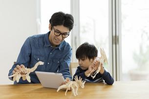 恐竜の模型で遊ぶ親子の写真素材 [FYI01733149]