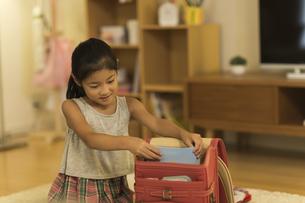 ランドセルに荷物を入れる女の子の写真素材 [FYI01733153]