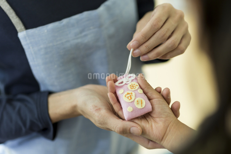 娘にお守りを渡す母親の写真素材 [FYI01733154]