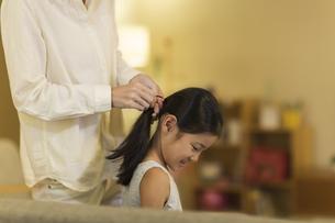 母親に髪を結んでもらう女の子の写真素材 [FYI01733209]