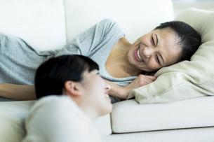 ソファーでくつろぐ母親と娘の写真素材 [FYI01733221]