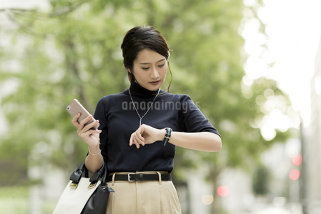 腕時計を見るビジネスウーマンの写真素材 [FYI01733230]