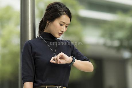 腕時計を見るビジネスウーマンの写真素材 [FYI01733242]