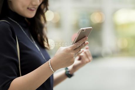 スマートフォンを見る若い女性の写真素材 [FYI01733249]