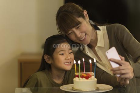 スマートフォンで写真を撮る親子の写真素材 [FYI01733279]
