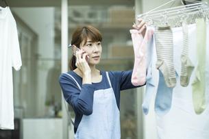 電話をしながら洗濯物を干す女性の写真素材 [FYI01733304]