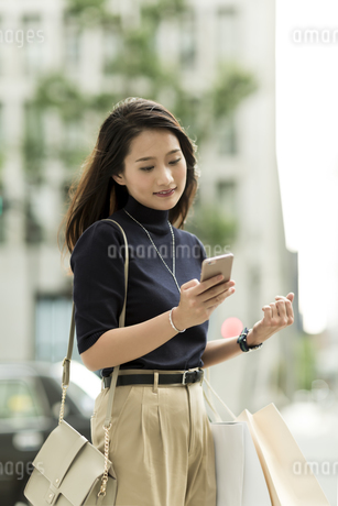 スマートフォンを見る若い女性の写真素材 [FYI01733341]