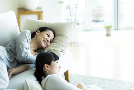 ソファーでくつろぐ母親と娘の写真素材 [FYI01733407]