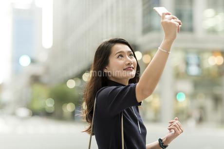 スマートフォンで撮影をする若い女性の写真素材 [FYI01733409]