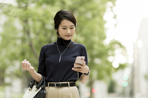 スマートフォンを操作するビジネスウーマンの写真素材 [FYI01733418]
