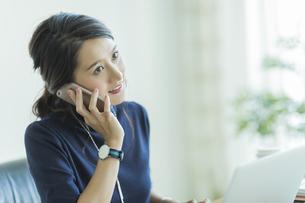 スマートフォンで通話をするビジネスウーマンの写真素材 [FYI01733425]