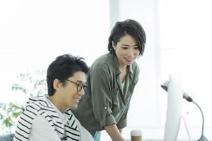 パソコンを見るビジネスマンとビジネスウーマンの写真素材 [FYI01733434]