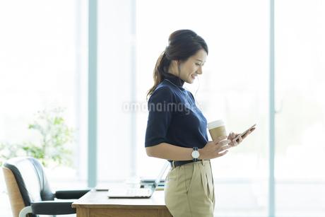 スマートフォンを操作するビジネスウーマンの写真素材 [FYI01733443]