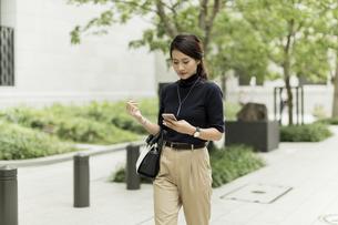 スマートフォンを見ながら歩くビジネスウーマンの写真素材 [FYI01733445]