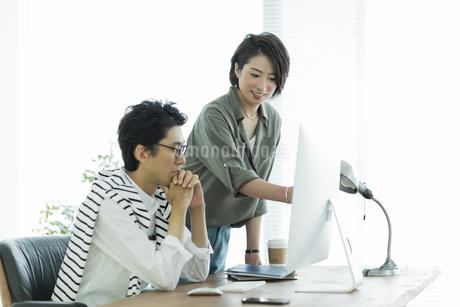 パソコンを見るビジネスマンとビジネスウーマンの写真素材 [FYI01733451]