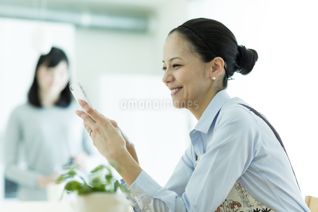 スマートフォンを見る母親の写真素材 [FYI01733455]