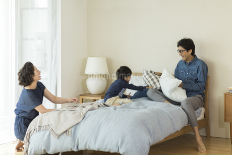 ベッドの上で遊ぶ家族の写真素材 [FYI01733471]