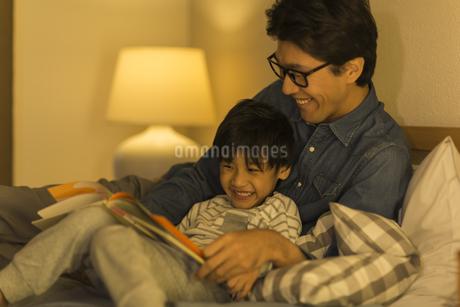 ベッドで絵本を読む父親と息子の写真素材 [FYI01733481]