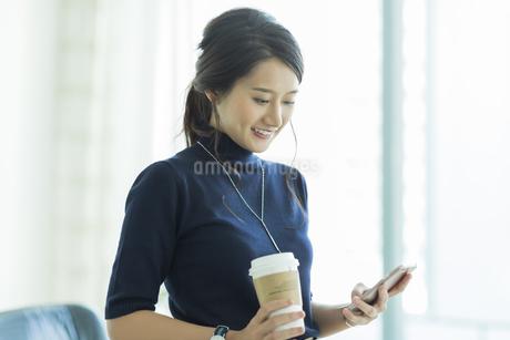 スマートフォンを操作するビジネスウーマンの写真素材 [FYI01733494]
